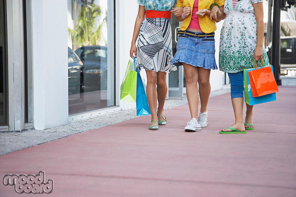 Three teenage girls (16-17) carrying shopping bags walking on street low section