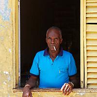Hombre asomado en una ventana en Isla de Carmen de Raton, estado Amazonas, Venezuela. Man peeking at a window in Isla de Carmen de Raton, Amazonas state, Venezuela.