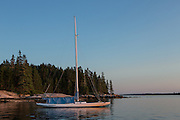 Center Harbor, Maine - 9 August 2014. Sailboat Butterfly at anchor at sunset.