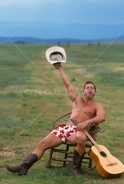 man in cowboy boots and underwear sitting in a chair in the country yelling