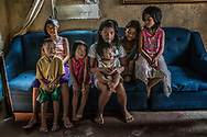These seven children were orphaned when Constantino de Juan, a Methampethamine user, was executed in front of this sofa - the hole in the sofa on the right was made by the bullet that passed through his body.  Now their 84 year old grandmother, Remy Fernandez must raise them all because their mother is in prison on drug charges.  Payatas, Metro Manila, Philippines