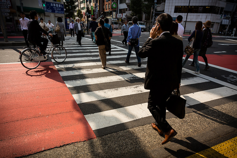 In the Tokyo morning, a typical japanese businessman crosses the street on his way to work.
