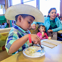 Jayden Yazzie, left, enjoys some cake as Haley, center, eats an ice cream cone next to her mother Marissa Yazzie at a McDonald House of New Mexico anniversary at the east-side McDonalds in Gallup Wednesday.
