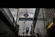 Commuter exits Westminster Underground station on Whitehall with the Way Out sign and arrow.