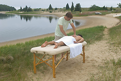Man being massaged outside beside a calm bay in East Hampton,NY