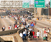 People affected by Hurricane Katrina walk on the elevated freeway in downtown New Orleans August 31, 2005. Authorities struggled on Wednesday to evacuate thousands of people from hurricane-battered New Orleans as food and water grew scarce and looters raided stores, while U.S. President George W. Bush said it would take years to recover from the devastation.