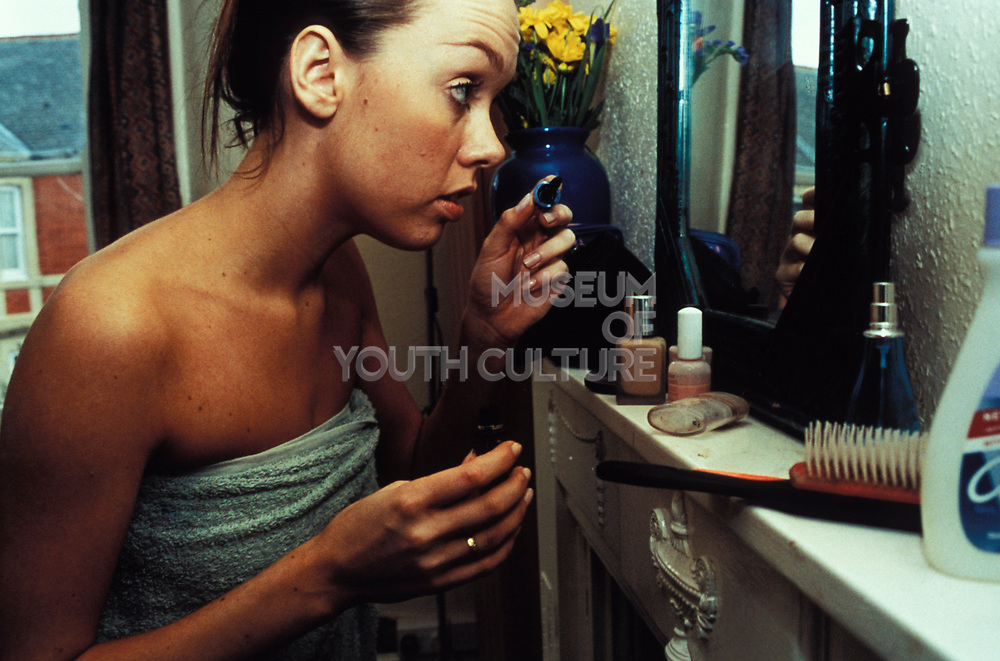 Tanned woman applying make-up, wrapped in towel in hotel suite, Paris, France, 1990s.