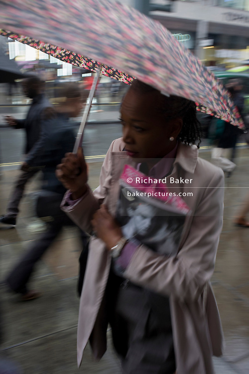 A Londoner walks along central London's Oxford Street during autumnal rain.