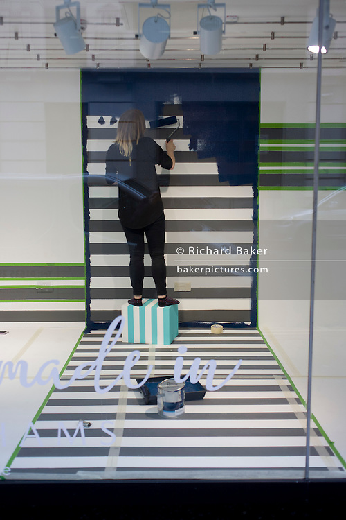 A window dresser prepares a new window design with a stripes theme in the Oxford Street branch of retailer Debenhams.