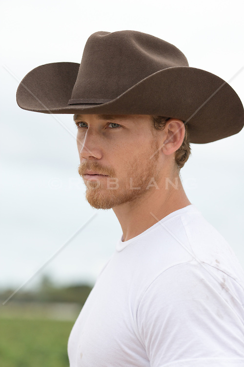 portrait of a rugged and handsome cowboy outdoors