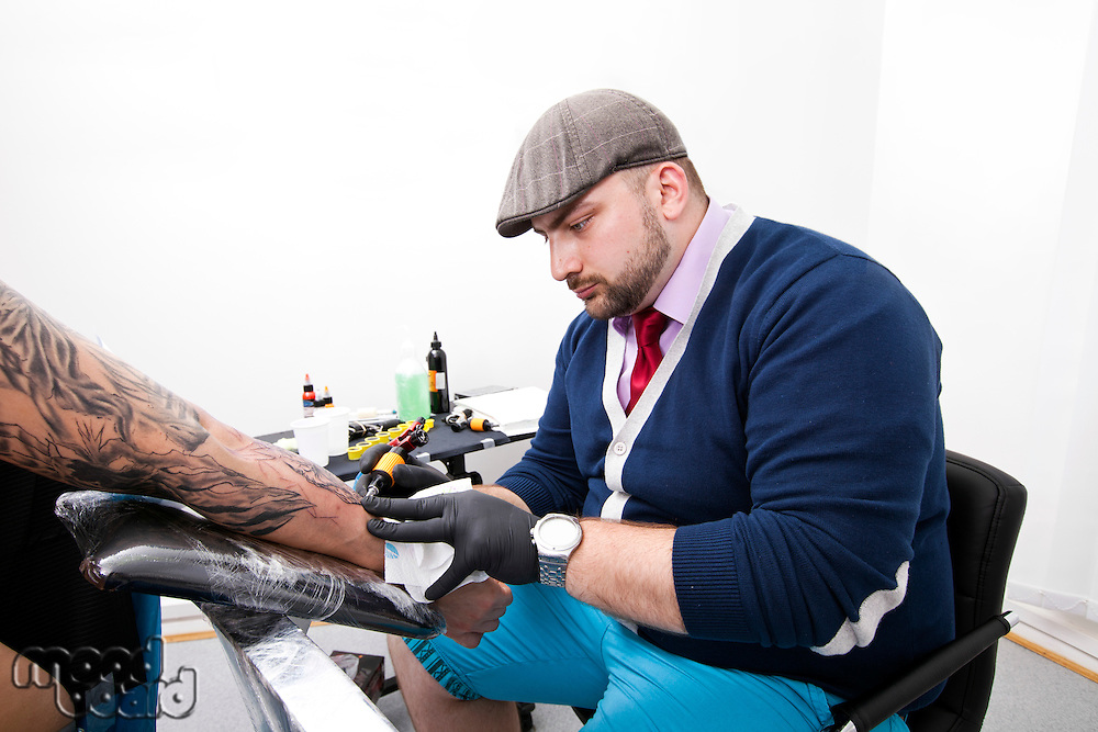 Young tattoo artist tattooing man's arm in studio
