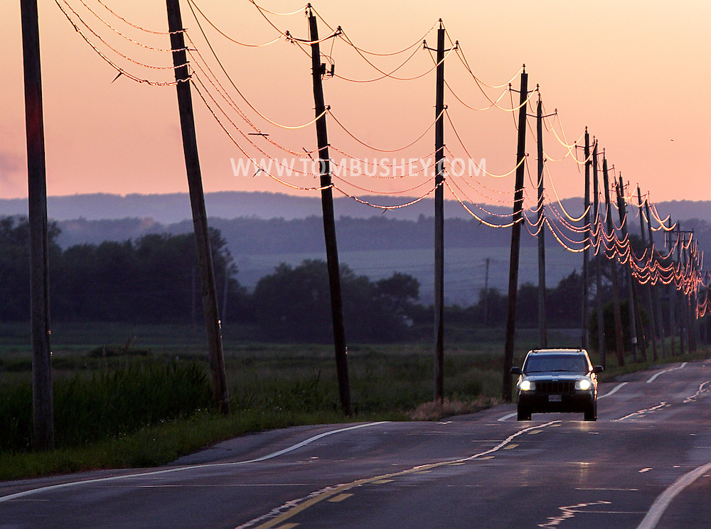 A car drives down Pumpkin Swamp Road in Florida, N.Y., at sunset on Friday, June 14, 2013.