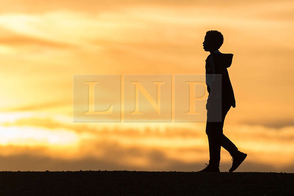 © Licensed to London News Pictures. 01/08/2018. LONDON, UK. A man watches a glorious sunset from Northala Fields in Northolt, west London, after a warm day.  The forecast is for temperatures rising to the 30s C by the weekend.    Photo credit: Stephen Chung/LNP