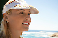 Woman in sun visor at beach head and shoulders close up