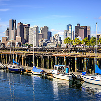 Boston skyline photo at Piers Park. Picture includes downtown Boston skyscraper buildings, old Boston Harbor piers, and boats.