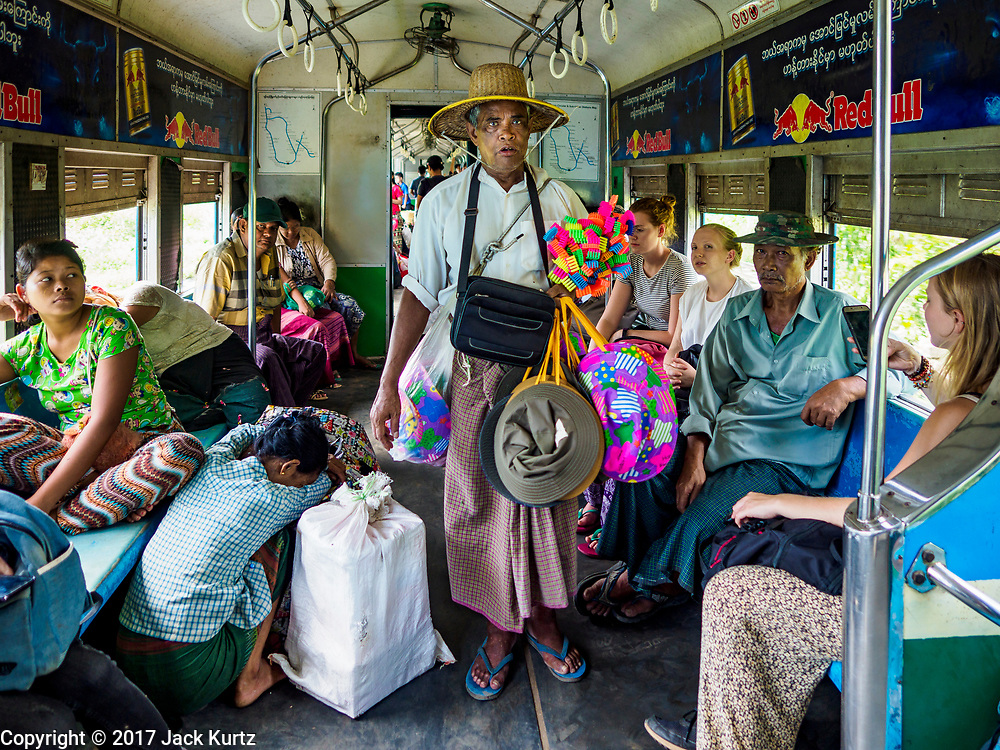 25 NOVEMBER 2017 - YANGON, MYANMAR: A man sells toys on the Yangon Circular Train. The Yangon Circular Train is a 45.9-kilometre (28.5 mi) 39-station two track loop system connects satellite towns and suburban areas to downtown. The train was built during the British colonial period, the second track was built in 1954. Trains currently run both directions (clockwise and counter-clockwise) around the city. The trains are the least expensive way to get across Yangon and they are very popular with Yangon's working class. About 100,000 people ride the train every day. A a ticket costs 200 Kyat (about .17¢ US) for the entire 28.5 mile loop.    PHOTO BY JACK KURTZ