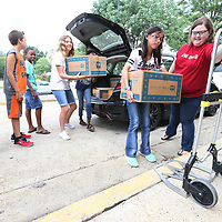 Jillian Babb, 11, helps unload boxes full of backpacks at Milam Elementary School on Friday. The backpacks are full of school supplies and will given to children who need help with the supplies.