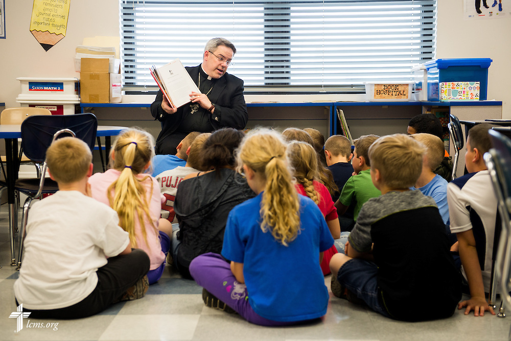 The Rev. Dr. Lee Hagan of St. Paul's Lutheran Church reads to students at St. Paul's Lutheran School in Concordia, Mo., on Thursday, April 10, 2014. LCMS Communications/Erik M. Lunsford