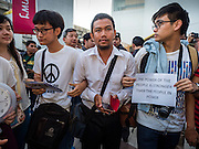 22 MAY 2015 - BANGKOK, THAILAND:  Anti-coup protestors lock arms during a protest in front of the Bangkok Art and Culture Centre Friday evening. The Thai military seized power in a coup on May 22, 2014. There were small protests throughout Bangkok Friday to mark the first anniversary of the coup. Police arrested protestors at several locations. The most serious protest was at Bangkok Art and Culture Centre (BACC) where about 100 protestors, mostly students, faced off against police for several hours. Police made numerous arrests at the BACC protest.    PHOTO BY JACK KURTZ