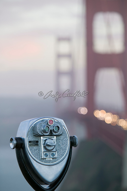 Binocular viewer on the Marin (Northern) side of the Golden Gate Bridge vista point at dusk. San Francisco, California
