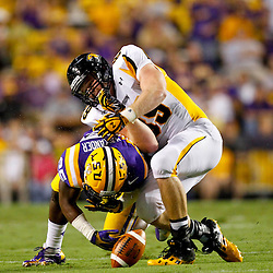 September 29, 2012; Baton Rouge, LA, USA; Towson Tigers tight end Tanner Vallely (89) fumbles as LSU Tigers linebacker Kwon Alexander (25) applies a hit during the second quarter of a game at Tiger Stadium.  Mandatory Credit: Derick E. Hingle-US PRESSWIRE