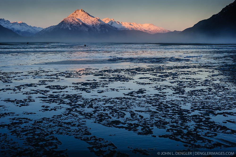 Ice forms on the Chilkat River as the sun bathes the mountains of Takhin Ridge including Chunekukleik Mountain in early morning sunlight at sunrise. The fog-like layer is blowing dust from the river's silt. During late fall, bald eagles congregate along the Chilkat River to feed on salmon. This gathering of bald eagles in the Alaska Chilkat Bald Eagle Preserve is believed to be one of the largest gatherings of bald eagles in the world.