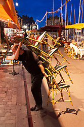 A waiter carrying chairs into a restaurant at the harbour in Honfleur, France