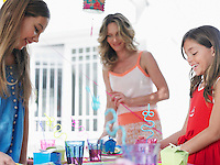 Mother and two daughters (7-9) (10-12) preparing birthday party