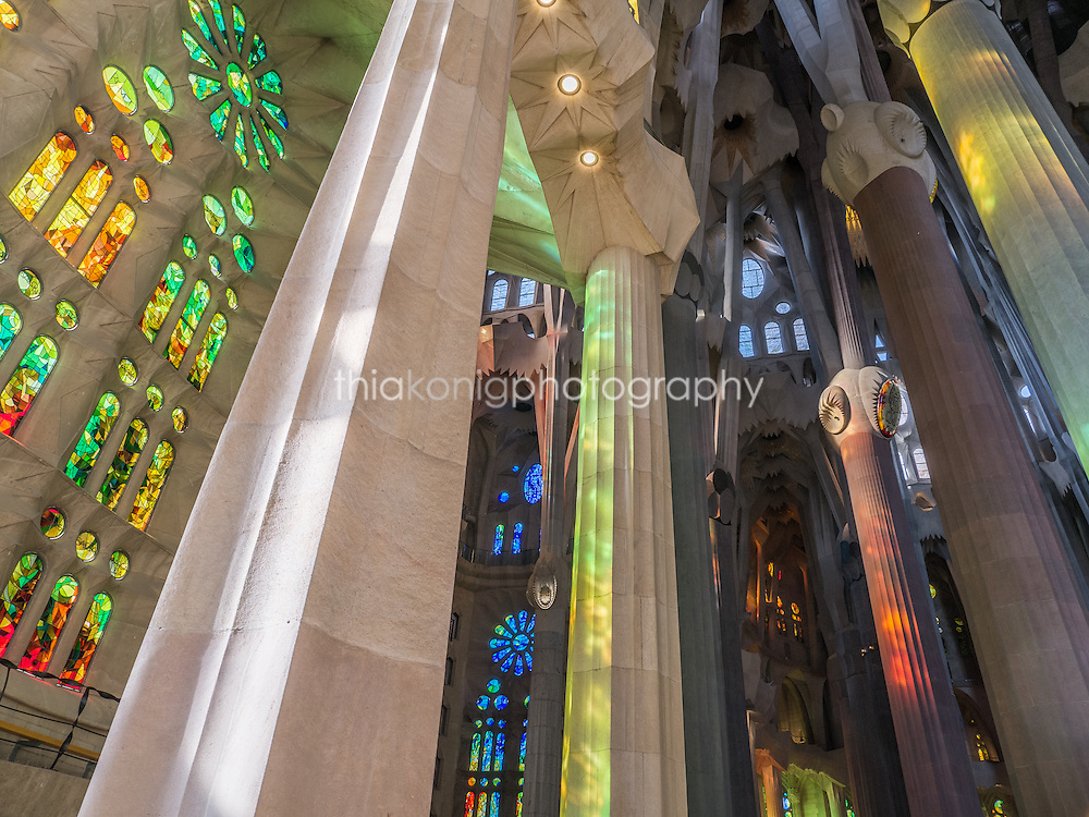 Stained glass windows cast colored light on the stone pillars inside La Sagrada Familia, Gaudi's unfinished architectural masterpiece, Barcelona, Spain.