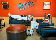 Orioles first baseman Chris Davis (19) and outfielder Chris Dickerson (60) lounge in the lobby of the Orioles baseball complex eiating for their turn with the team's video crew during Photo Day. Each spring training the players spend a morning in full uniform being photographed by various media outlets and the team's photographers.