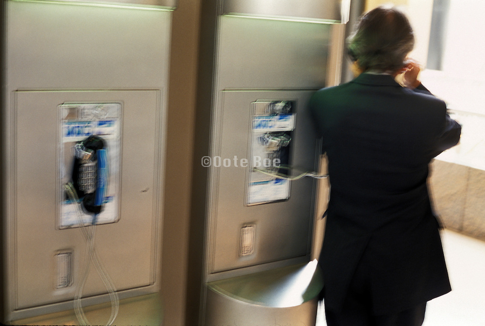 business man using a public phone.