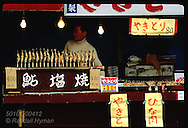 Vendor tends food booth where he sells fish-on-a-stick to passing tourists @ Lake Chuzenji Japan