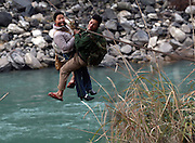 Gongshan, Yunnan, China - 19 JAN 2006 - A Lisu women holds her hier in her teeth as she crosses the Nu River with her husband on a cable and pulley in Yunnan Province. Secrecy continues to surround the controversial plan to build a series of big dams on the Nu River in Yunnan province. Now, Chinese media reports suggest the project is set to be rammed through without environmental-impact documents being made public or open hearings held, as required by law. Beginning high on the Tibetan plateau, the Nu River passes through southwest China before entering Burma, where it is known as the Thanlwin (in Burmese) or the Salween (in English). The 2,800-kilometre river forms Burma's border with Thailand for 120 km, and eventually empties into the Andaman Sea. The free-flowing status of the Nu, one of only two major rivers in China uninterrupted by dams, is under serious threat from all three of the countries it passes through.