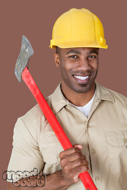 Portrait of young African man holding axe on shoulder over colored background