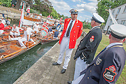 The Royal Swan Uppers, who wear the scarlet uniform of Her Majesty The Queen, travel in traditional rowing skiffs together with Swan Uppers from the Vintners' and Dyers' livery companies. They are led by David Barber, the Queen's Swan Marker. Swan Upping plays an important role in the conservation of the mute swan and involves The Queen's Swan Warden collecting data, assessing the health of young cygnets and examining them for any injuries. Cygnets are extremely vulnerable at this early stage in their development and Swan Upping affords an opportunity to help both adults and cygnets that might otherwise go untreated. The River Thames, London, UK.