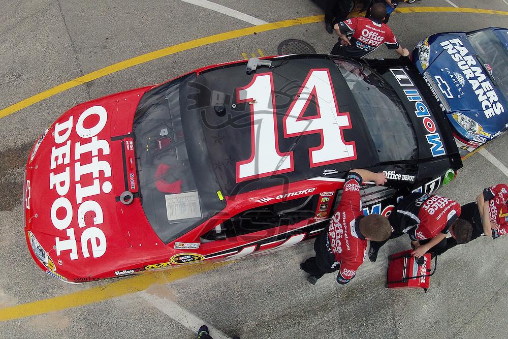Daytona Beach, FL - FEB 19, 2012: Crew members of  Tony Stewart (14) work on the car before qualifying for the Daytona 500 at the Daytona International Speedway in Daytona Beach, FL.