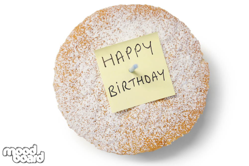 High angle view of 'happy birthday' note on powdered sugar sponge cake