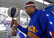 "Harlem Globetrotters' Brawley ""Cheese"" Chisholm teaches visitor Tyler Scott, 7, of Ridgeland, Miss., how to twirl a basketball on his finger aboard the new Atlanta Streetcar during a tour of downtown sights in advance of a pair of upcoming dates for shows at the Arena at Gwinnett, on Monday, March 9, 2015, in Atlanta. David Tulis / AJC Special"