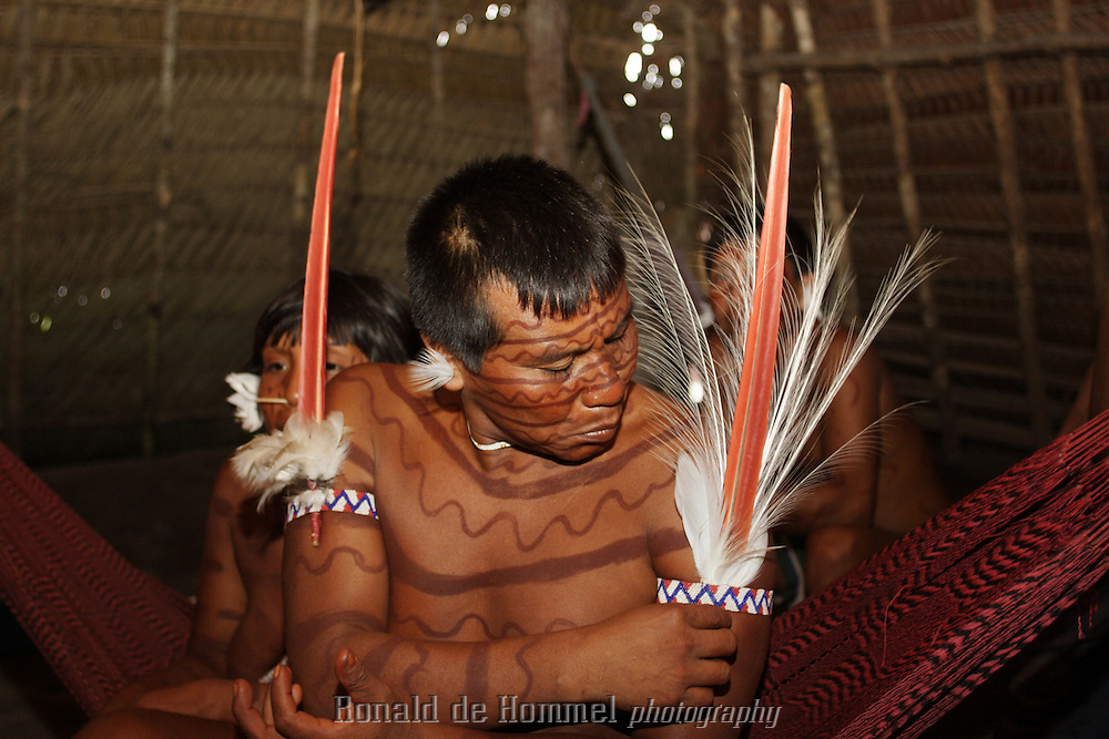 Viriunaveteri, Venezuela. Yanomami tribal leader arranging his costume inside a hut..The village of Viriunaveteri consists of 15 huts around a muddy square. It's situated in the Venezuelan Amazone several days by boat from the nearest town. This community on the banks of the Casiquiare is one of the few Yanomami villages that actually has some contact with the outside world. Most other tribes live deeper in the jungle.