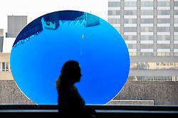 "© Licensed to London News Pictures. 25/09/2018. LONDON, UK.  A woman walks by ""Sky Mirror, Blue"", 2016, by Anish Kapoor.  Preview of ""Space Shifters"" at the Hayward Gallery, an exhibition which features artworks by 20 leading international artists that disrupt the visitor's sense of space and alter their perception of their surroundings.  The show runs 26 September to 6 January 2019.  Photo credit: Stephen Chung/LNP"