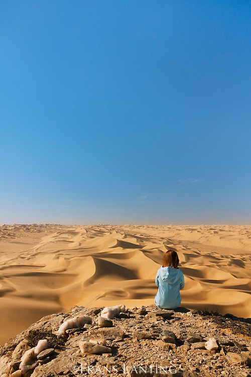 Woman overlooking sand dunes, Namib-Naukluft National Park, Namibia, Model release