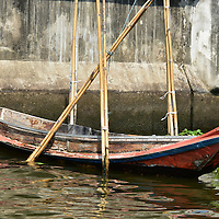 Wood Canal Boat Tied To Bamboo Stalks in Bangkok, Thailand <br />