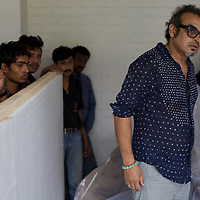 "Subodh Gupta, contemporary artist in his studio in Gurgaon with freight staff about to collect a sculpture for delivery to a European exhibition.  ..Gupta's most celebrated sculptures are constructed from common domestic items including the steel pots and pans that are a feature every Indian home. Of the kitchen-ware that forms the basis of his work, Gupta says,..""The poor, the middle class and the rich use it at home. In this country, how many people have the utensils but they starve because there is no food?""..Gupta was brought up, one of six children, to a railway-worker father in a north Indian village. ..Gupta's work fetches such huge sums of money. Two versions of his Mind Shut Down, modeled on the human skull and constructed entirely of steel kitchen utensils recently sold for EUR1 million each...Photo: Tom Pietrasik.Gurgaon, Haryana. India. .July 23rd 2009"