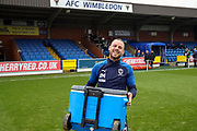 AFC Wimbledon fitness coach Jason Moriarty carrying box onto pitch for warm up during the EFL Sky Bet League 1 match between AFC Wimbledon and Southend United at the Cherry Red Records Stadium, Kingston, England on 1 January 2020.