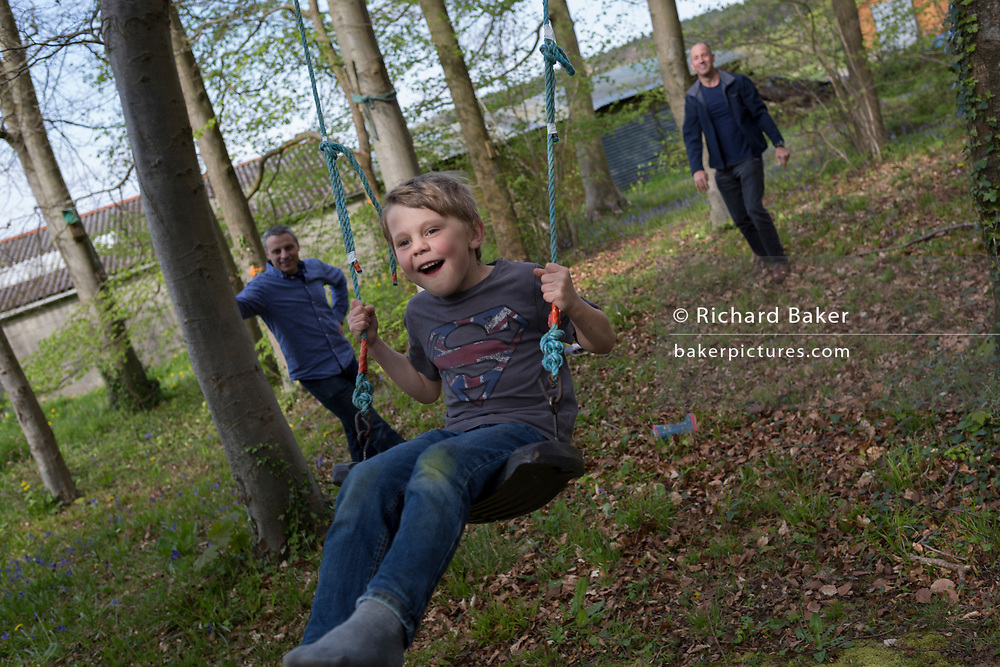 A 7 year-old boy plays on a swing with family members in local woods, on 23rd April 2017, in Wrington, North Somerset, England.