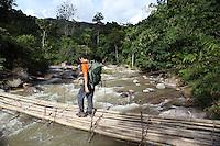 Traveller crossing a bamboo bridge.