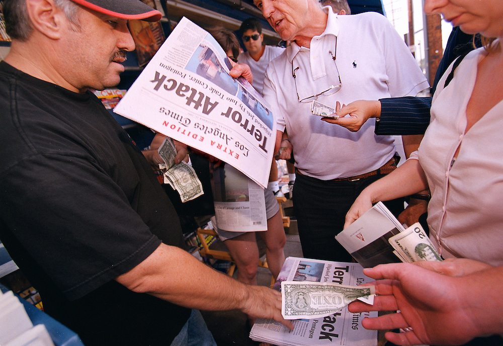 Los Angeles residents gather around a news stand to grab an Extra Edition detailing the terrorist attacks on 9/11.