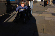 A young boy in a pushchair yawns during an exhausting daytrip to London.