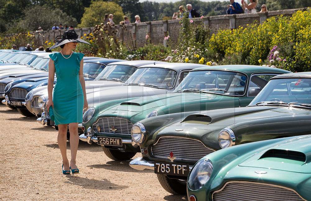 © Licensed to London News Pictures. 02/09/2017. London, UK. A visitor admires a long line of vintage Aston Martins on display at the Concours of Elegance show in the grounds of Hampton Court Palace. The Concours of Elegance brings together, over three days, a selection of 60 of the rarest cars from around the world some of which have never been seen before in the UK. Each car owner is asked to vote on the other models on display to decide which car is considered to be the 'Best of Show'. The show also displays of hundreds of other fine motor cars, including entrants to The Club Trophy. Photo credit: Peter Macdiarmid/LNP