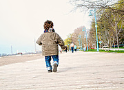 A young boy walking down boardwalk with his back to camera.
